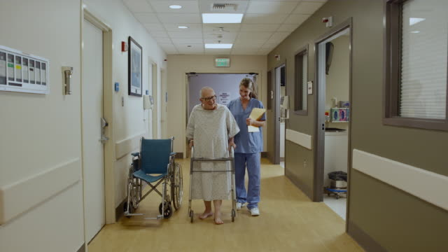 ws nurse assisting patient walking down hospital hallway using walker / edmonds, washington, usa - kvinnlig sjuksköterska bildbanksvideor och videomaterial från bakom kulisserna