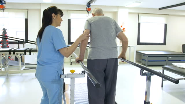 Nurse assisting senior man in walking between bars