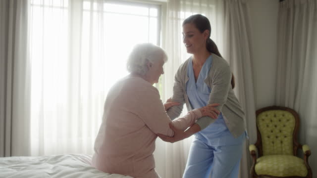 nurse assisting senior woman in walking at home - uniform stock videos & royalty-free footage
