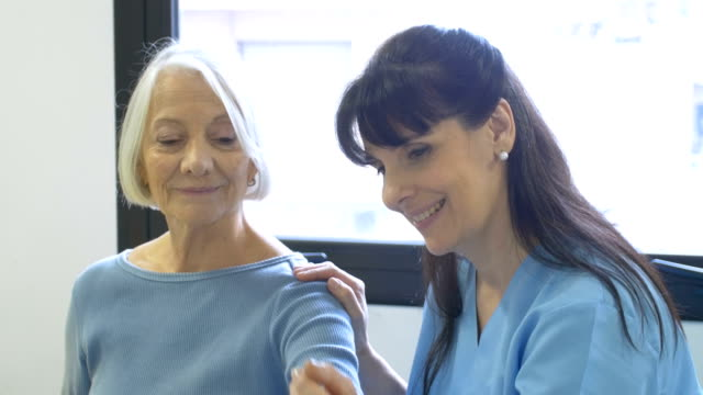 Nurse assisting senior woman with hand exercise