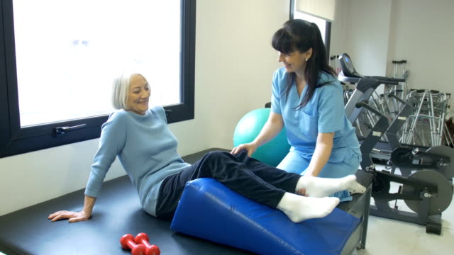 Nurse assisting senior woman with leg exercise