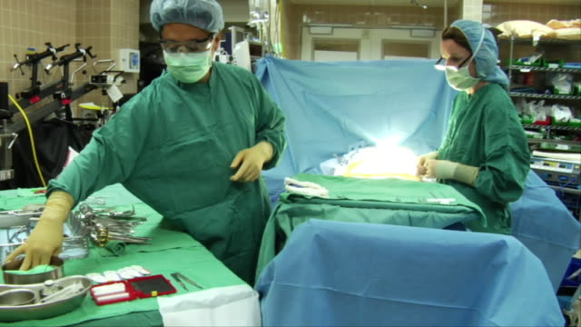 MS, Nurse assisting surgeon during surgery in operating room, Berkeley, California, USA