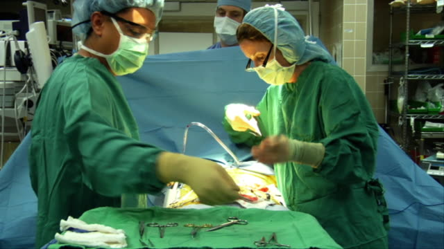 MS, Nurse assisting surgeon during suturing patient in operating room, anesthesiologist standing in background Berkeley, California, USA