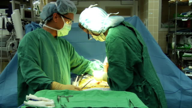 MS, Nurse assisting surgeon during suturing patient in operating room, Berkeley, California, USA