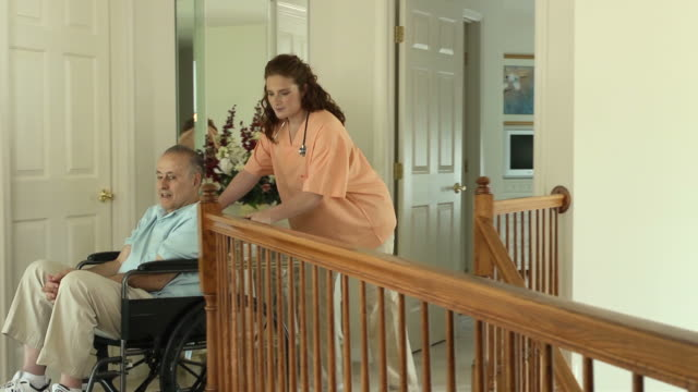 nurse assisting wheelchair bound male in home - house call stock videos and b-roll footage