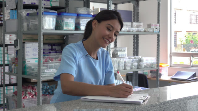 nurse at the pharmacy taking notes on documents - checklist stock videos & royalty-free footage