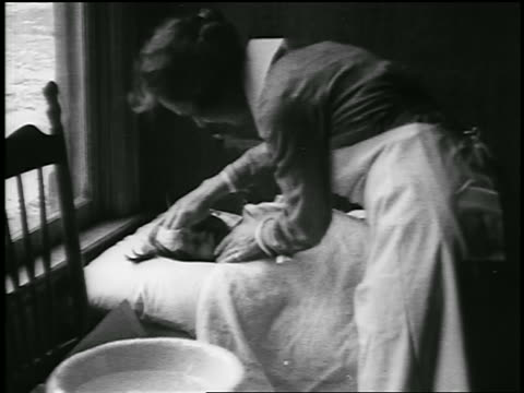 b/w 1920 nurse attending to sick girl lying in hospital bed / detroit, michigan / newsreel - 1920 stock-videos und b-roll-filmmaterial
