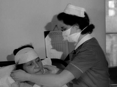 a nurse bandages a patients head on a hospital ward - 包帯点の映像素材/bロール