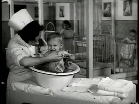 nurse bathing crying baby in small tub babies in cradle bg ms baby sleeping on stomach in cradle ms baby dancing against cradle bars ms angry baby... - föräldralös bildbanksvideor och videomaterial från bakom kulisserna