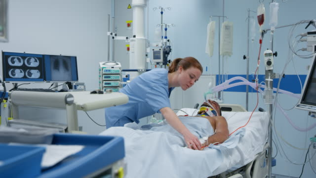 ICU nurse checking a young male patient on the mechanical ventilation