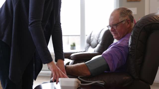 vídeos y material grabado en eventos de stock de enfermera revisando la presión arterial de un anciano en casa - colesterol