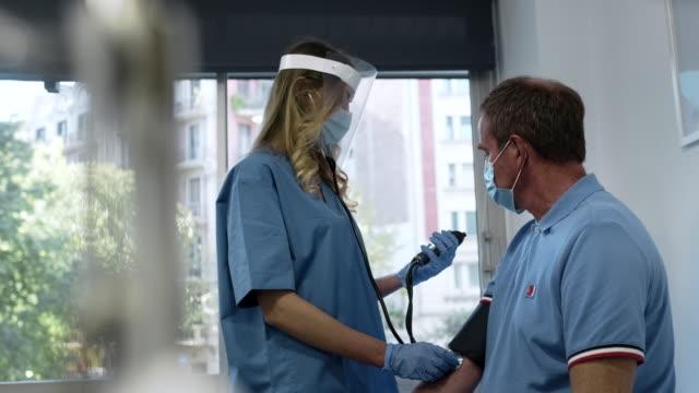 vídeos y material grabado en eventos de stock de una enfermera revisando la presión arterial de un anciano. - médico de cabecera