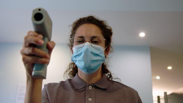 krankenschwester überprüft temperatur mit einer infrarotpistole - temperatur stock-videos und b-roll-filmmaterial