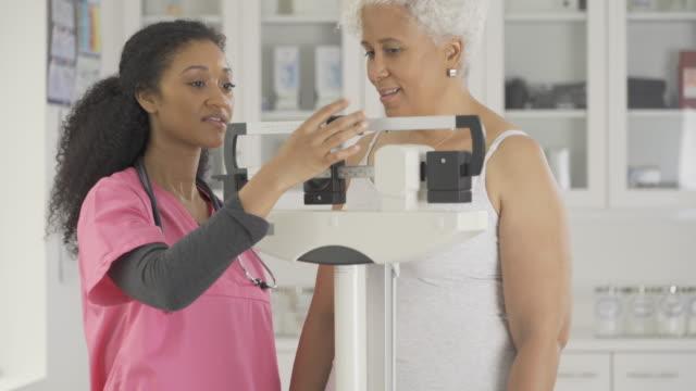 Nurse Checking Weight of Senior Patient