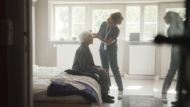 nurse combing hair of senior woman at home - bathrobe stock videos & royalty-free footage