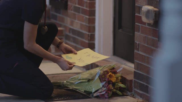 nurse comes home to flowers and thank you sign - blumenbouqet stock-videos und b-roll-filmmaterial