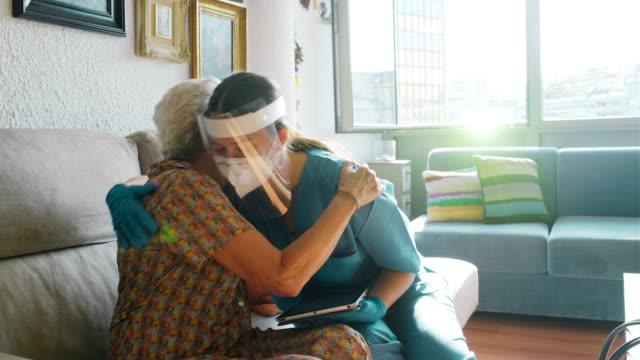 老婦人を慰め、covid調査を行う看護師。 - 福祉点の映像素材/bロール