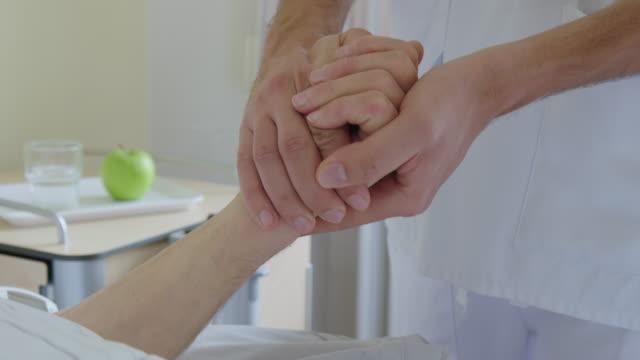 vidéos et rushes de infirmière réconfortant le patient après le contrôle de tension artérielle vers le haut - infirmier