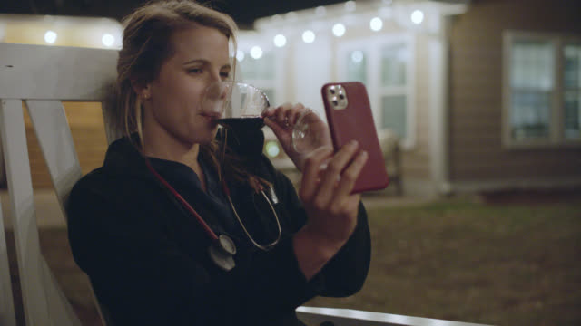 nurse drinking wine and video chatting with friends after work. - happy hour video stock e b–roll