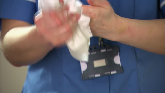 Nurse drying her hands after washing
