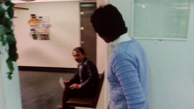 1983 montage nurse escorting patient from waiting area into exam room / london, england - 国民保険サービス点の映像素材/bロール