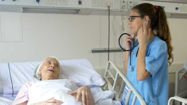 nurse examining senior patient with stethoscope - stetoscopio video stock e b–roll