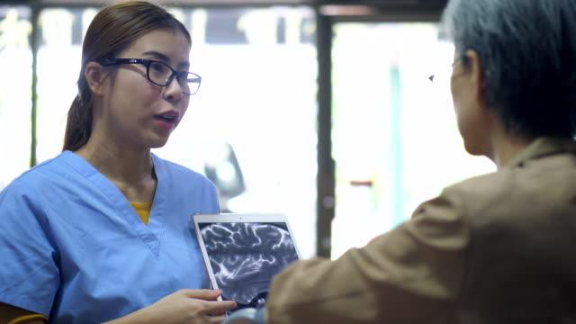 vídeos y material grabado en eventos de stock de enfermera explicar a la mujer de la tercera edad - enfermedad de alzheimer