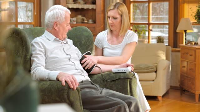 Nurse explaining blood pressure measuring to senior man at home