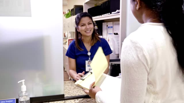 nurse explains medical document to patient in doctor's office - form filling stock videos & royalty-free footage