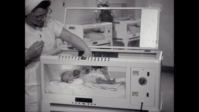 MS Nurse feeding water to baby in incubator in hospital ward / United States