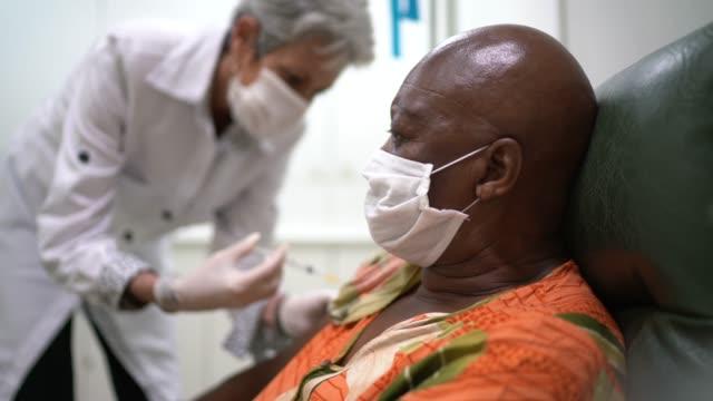 infermiera che dà un colpo di vaccinazione a un paziente - vaccini video stock e b–roll