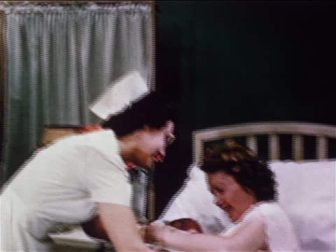 1950 nurse giving baby to woman in hospital bed / woman opening gown preparing to breast feed - breastfeeding stock videos and b-roll footage