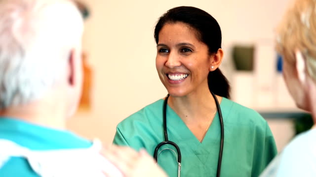 nurse giving good news to a senior patient and spouse - nurse stock videos & royalty-free footage