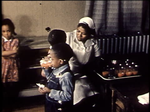1940 montage nurse giving medicine to children / united states - tomato juice stock videos and b-roll footage