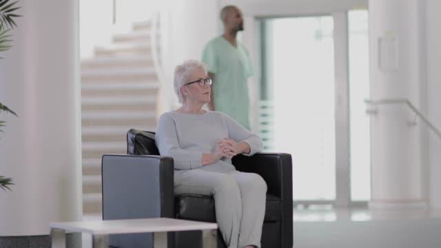 vidéos et rushes de nurse greeting patient in a waiting room - salle attente