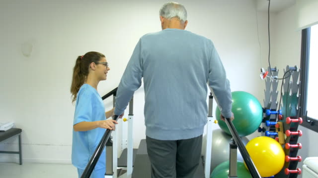 nurse guiding patient to walk on slope in rehab - physiotherapy stock videos & royalty-free footage