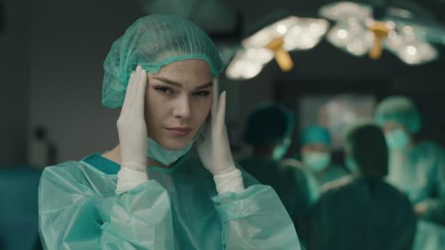 nurse having headache in operating room - mental burnout stock videos & royalty-free footage