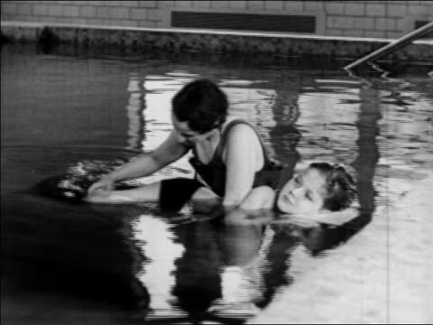 b/w 1934 nurse helping boy with polio in pool move legs in water therapy / indiana / newsreel - 1934 stock-videos und b-roll-filmmaterial