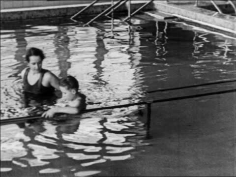 b/w 1934 nurse helping boy with polio walk in pool during water therapy / indiana / newsreel - patientin stock-videos und b-roll-filmmaterial