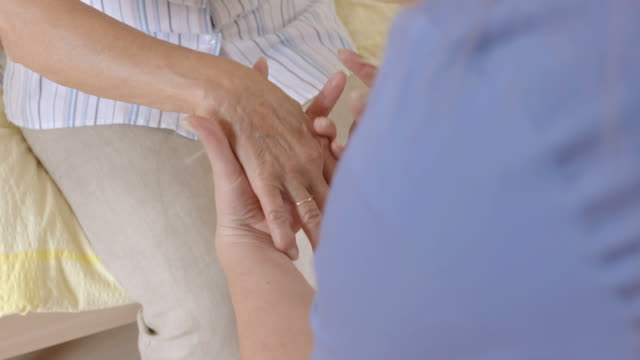 HD: Nurse Helping Elderly Woman To Stand Up