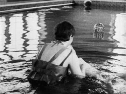 b/w 1934 nurse helping little girl with polio move arms in pool in water therapy / indiana / newsreel - patientin stock-videos und b-roll-filmmaterial