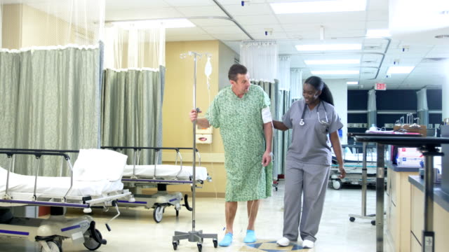 nurse helping patient walk after medical procedure - hospital gown stock videos & royalty-free footage