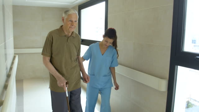 nurse helping senior man in using cane