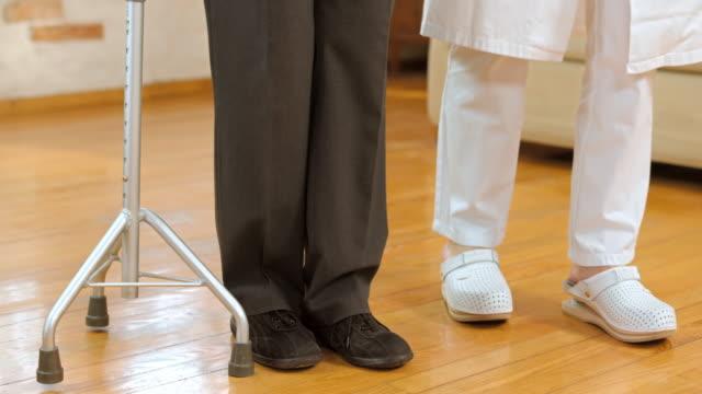 DS nurse helping senior man use tripod walking stick