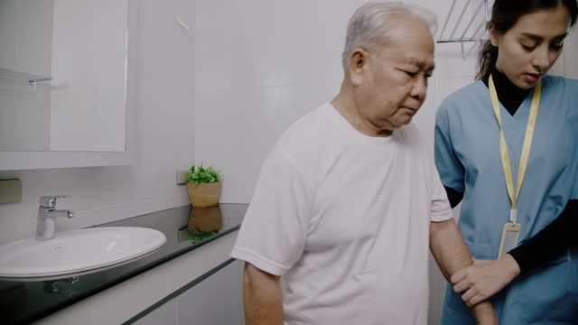 nurse helping senior man walking out of bath room. - healthcare worker stock videos & royalty-free footage