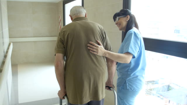 Nurse helping senior patient in using mobility walker