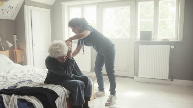 nurse helping senior woman to remove bathrobe - bathrobe stock videos & royalty-free footage