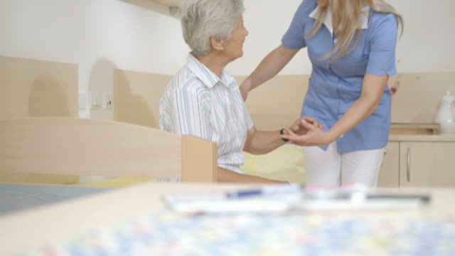 hd dolly: nurse helping senior woman to stand up - care stock videos & royalty-free footage