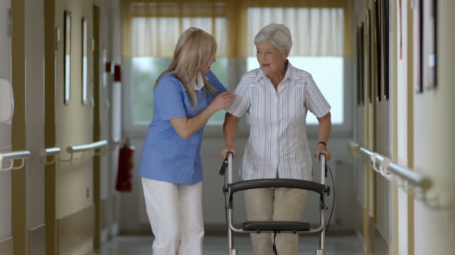 HD: Nurse Helping Senior Woman With Walker