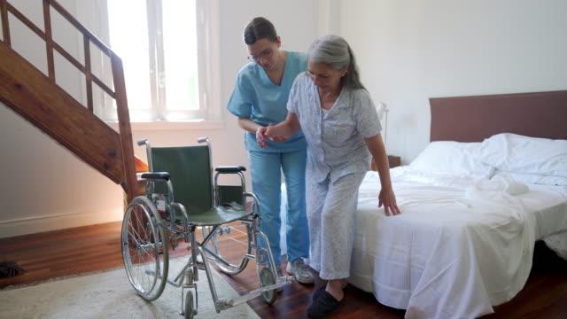 vídeos de stock e filmes b-roll de nurse helping senior woman with wheelchair in nursing home - chamada a casa